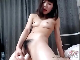 Horny Asian college girl fucks ourselves with dildo at digs